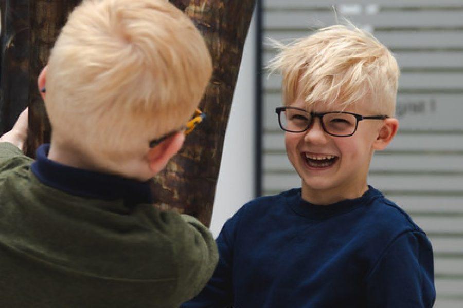 To barn med briller leker og ler.